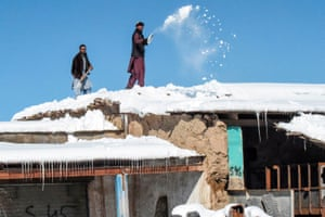 Workers remove snow from a hotel roof in Pakistan's Balochistan province