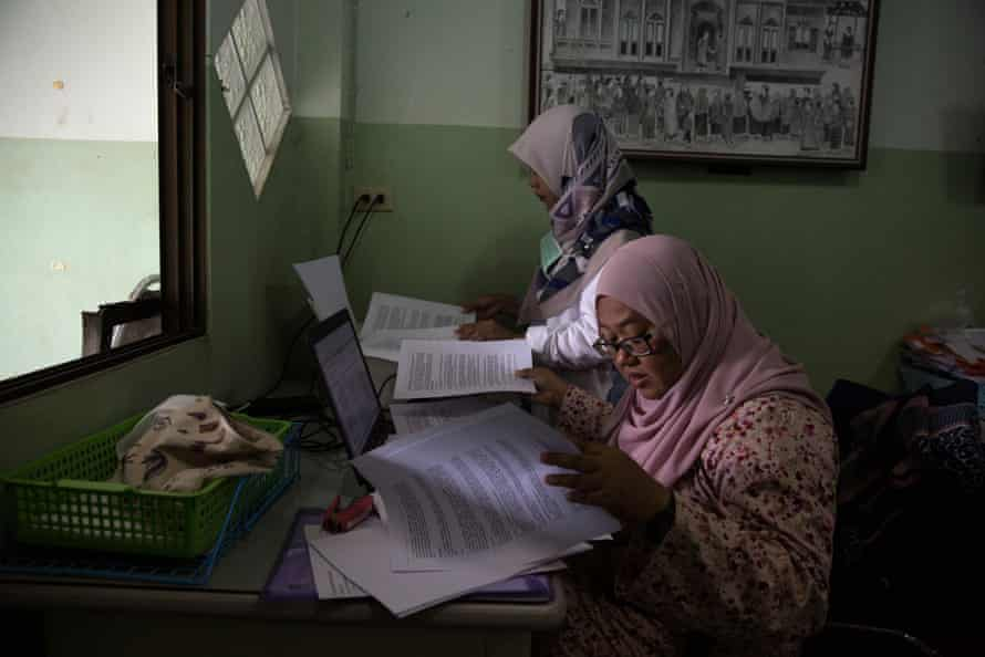 Anchana Heemmina and another woman work on a report in an office