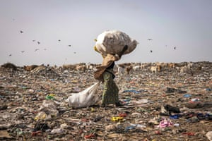 Dakar: a waste picker walks with recyclable waste on her head in the Mbeubeuss rubbish dump