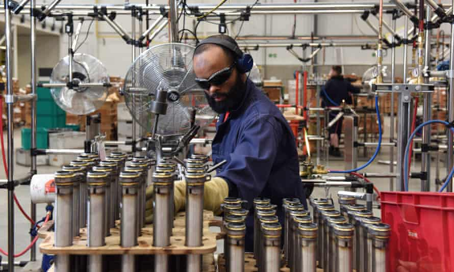 A factory worker brazes bicycle parts