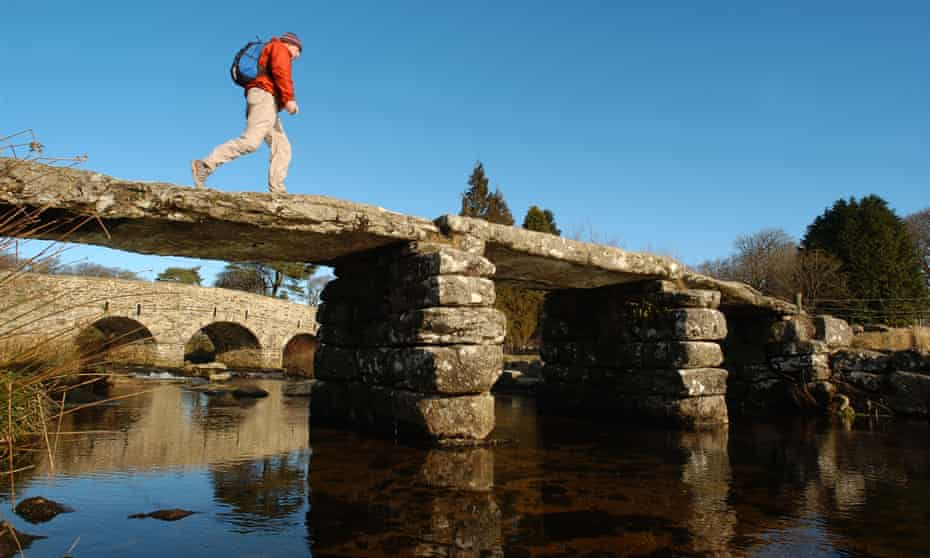 Man hiking across a stone bridge in Dartmoor