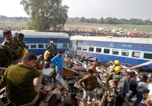 Rescue workers search for survivors at the site of a train derailment that killed more than 100 people south of Kanpur city
