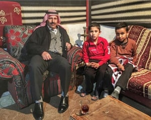 Mahmoud and his two sons sit on a sofa and chair at his home in Jordan. Mahmoud looked after Leon McCarron with feet washing, dinner and a place to stay.