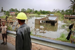 Locals stand near the flooded village of Tica, central Mozambique.