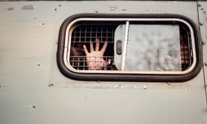 A supporter of the opposition Movement for Democratic Change is taken away in a prison van in Harare