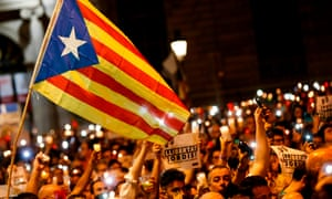 Protesters carry a Catalan pro-independence flag in Barcelona after the arrest of two separatist leaders.
