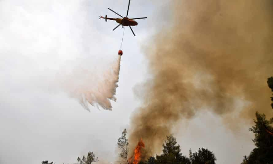 A helicopter pours water on a wildfire near the village of Kechries in Greece.