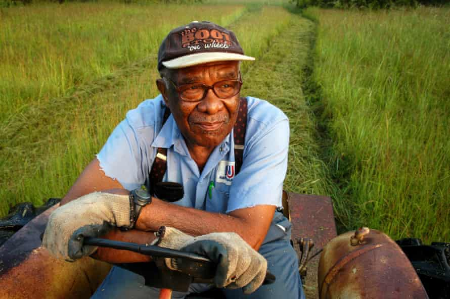 Eddie Cotton, 82, Hermanville, MS, clears a field for a fall crop of hay, using a 40-year-old tractor. He is among thousands of Black farmers denied federal loans in past years. 'They took away my ability to provide for my family,' he says.