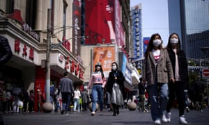 People out shopping in Shanghai after the city's emergency alert level was downgraded