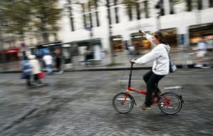 A woman rides her bicycle on the Champs-Élysées in Paris