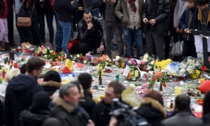 A man looks at flowers, messages and candles layed in tribute to victims in Brussels.