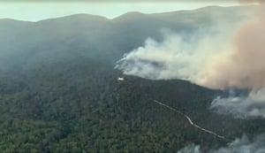 A plane flies over a burning Fraser Island.