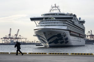 A port worker runs in front of the Diamond Princess cruise ship