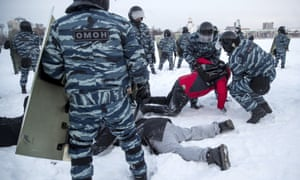 Police with riot shields and camouflage uniforms prevent two people from lying in the snow