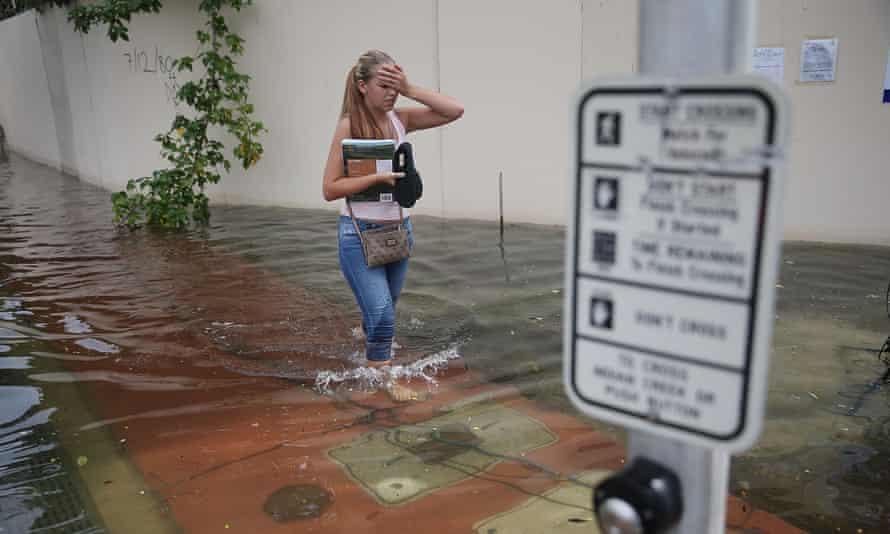 A woman walks through a flooded street that was caused by the combination of the lunar orbit which caused seasonal high tides and what many believe is the rising sea levels due to climate change, in September in Miami Beach, Florida.