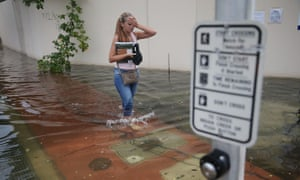 A woman walks through a flooded street in Miami Beach. The flood was caused by the combination of the lunar orbit, which generated seasonal high tides, and what many believe is the rising sea levels due to climate change.