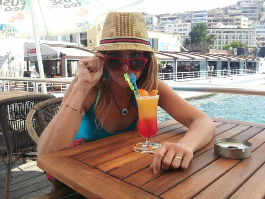 Lisa Bench sips a colourful drink while wearing a hat and sunglasses