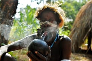 An elderly woman from the Suri tribe smokes a pipe