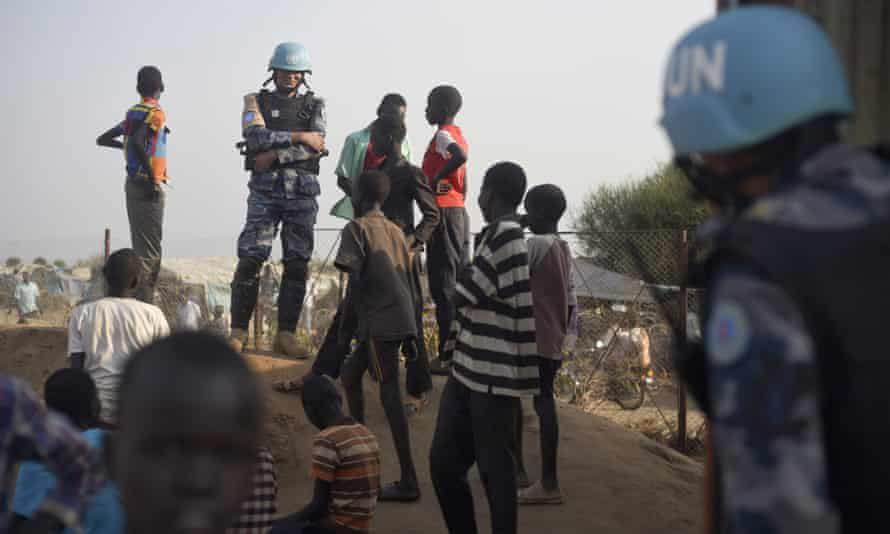 United Nations peacekeepers standing with displaced children at the UN base in the capital Juba.