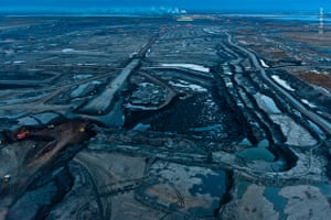 Twilight falls on the Alberta tar sands, the landscape takes on an oily blue tint