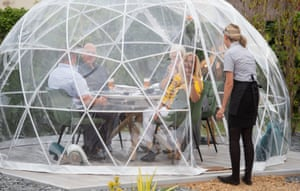 A waiter checks on diners in the outdoor dining pods at the Barn restaurant in Terrington St John, Norfolk, England.