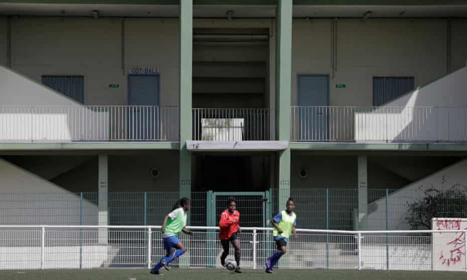 Teenage girls of Racing Club de Saint-Denis women's football club playing behind the Stade Auguste Delaune