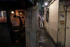A man walks along a narrow alleyway