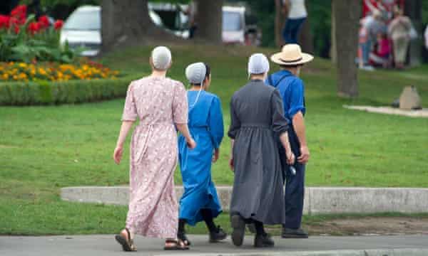 Mennonite girls with father walking on a street in Niagara Falls, Ontario, Canada.