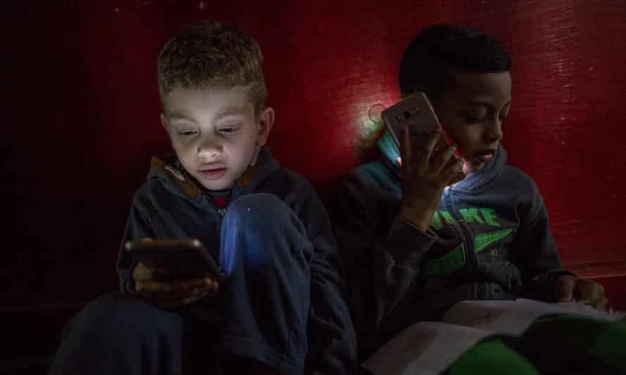 Children of the Mauá Occupation play with mobile phones