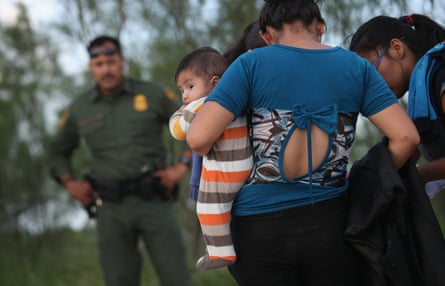 Families of Central American immigrants turn themselves in to US Border Patrol agents after crossing the Rio Grande river from Mexico to McAllen, Texas