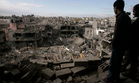 Palestinians look down on the destroyed house of a Hamas militant after an Israeli airstrike in the Gaza Strip, 2 January 2009