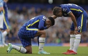 Cesar Azpilicueta of Chelsea checks on Reece James who is down injured.