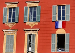 French flags hang on windows of a building in Nice, southern France