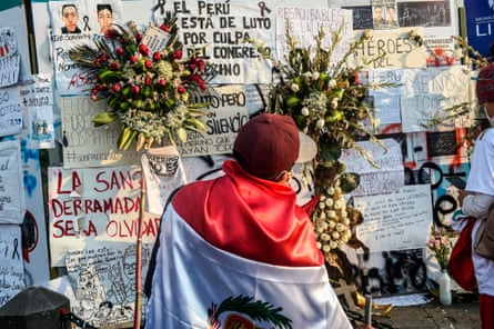 A man wearing a Peruvian flag stands in front of a mural in honour of Inti Sotelo and Bryan Pintado, two victims killed in recent protests.