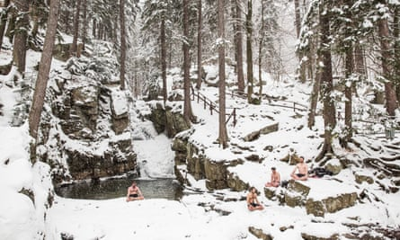 Four men sitting and meditating in the snow in their shorts