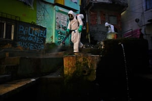 A volunteer disinfects an area inside the Santa Marta favela during the Covid-19 pandemic.