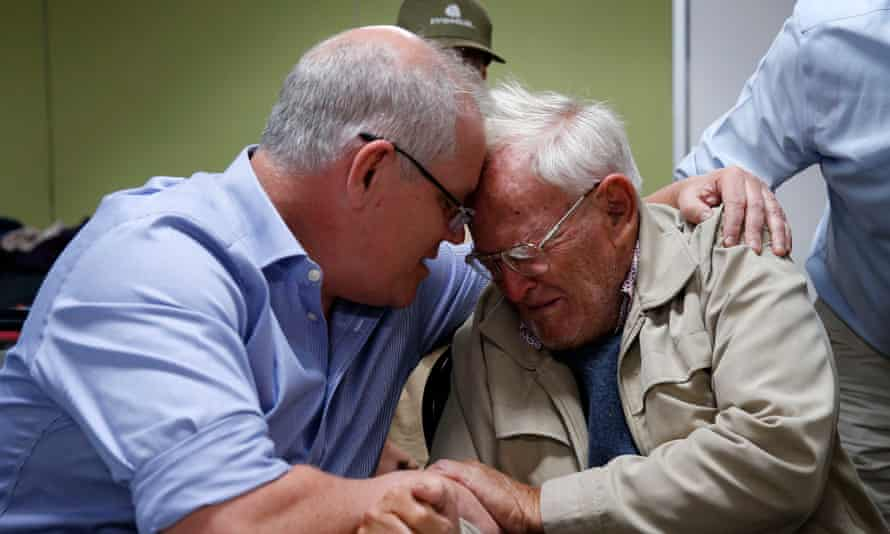 Scott Morrison comforts 85-year-old Owen Whalan, who was evacuated from his home to the Taree evacuation centre