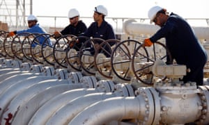 Workers adjust the valves of oil pipes at West Qurna oilfield in Iraq.