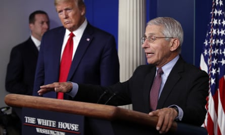 Donald Trump listens as Anthony Fauci speaks at the White House, in April.