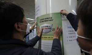 """Workers from the Seoul Metro put up a banner reading """"People who do not wear masks in public will face a 100,000 won (US$90) fine"""", at a subway station in Seoul, South Korea, Friday, 13 November 2020."""