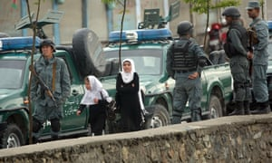 Schoolgirls walk past police forces near the blast site in Kabul