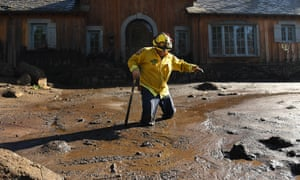Firefighter Alex Jimenez wades through the mud in Montecito after finding remains of a victim of the flash flood.