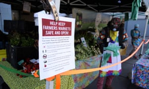 A sign about keeping the farmers market safe is posted on a vendor's tent during the Ferry Plaza Farmers Market in San Francisco.