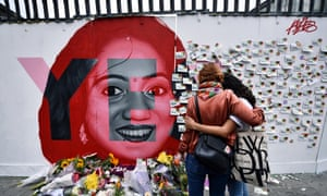 Two women look at written notes left on the Savita Halappanavar mural.=