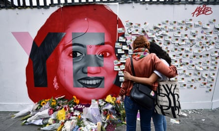 Two women console one another as they look at written notes left on the Savita Halappanavar mural in Dublin on Saturday