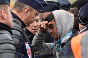 A young man shrinks under the gaze of a French police officer in riot gear as he and others wait in large queues to be taken away from Calais.