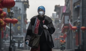 A Chinese woman wears a protective mask and gloves as she walks in a nearly empty and shuttered commercial street in Beijing on 12 February.