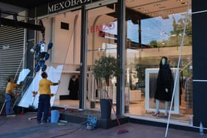 Workers replacing the broken window of a fur shop in central Athens today, after last night's clashes.