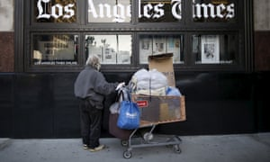 A homeless man outside the building of the Los Angeles Times newspaper. The number of homeless people in the county is up 25% from last year.