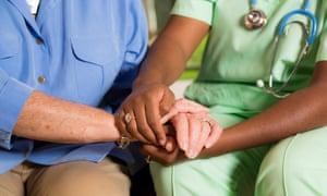 A nurse holding an older woman's hands